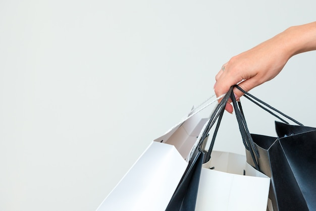 女性の手は、明るい灰色の背景に黒と白の買い物袋を保持します。
