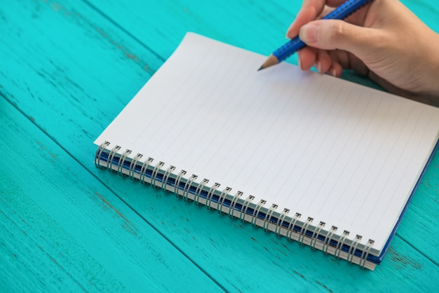 女の子は鉛筆を持って、ノートブック、青い木製のテーブルで将来の目標を書き留める準備をします。