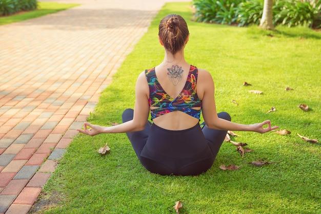 若いフィットネス女性が公園でヨガを練習します。健康的でアクティブなライフスタイル、スポーツのテーマ。