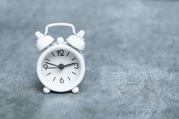灰色の背景に白のアナログ目覚まし時計、コピースペース。時間のテーマ