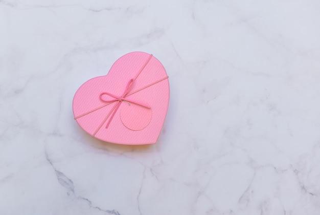 大理石の明るい灰色の背景、上面にハートの形のギフト用のピンク包装。バレンタインデー、愛、プレゼントのテーマ。
