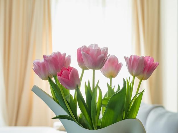 ウィンドウに対して水まき缶の形で花瓶にピンクのチューリップの花束