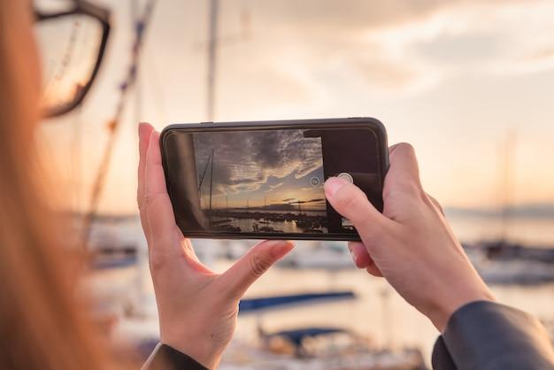 女の子は夕暮れ時のスマートフォンでヨットと港の写真を撮る。旅行、写真のテーマ。