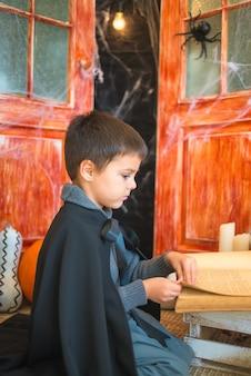 ハロウィーンの装飾背景に本を読んでカーニバルウィザード衣装で白人少年