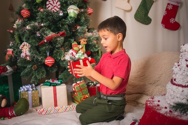 クリスマスツリーの背景にギフトボックスを見て驚きと喜びを持つ少年