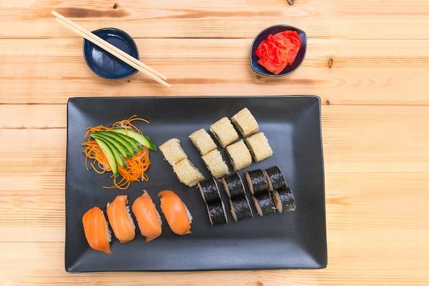 ロールと寿司のセットは、生姜と箸のピクルス、木製のテーブル背景、上面図が黒い長方形の皿の上。日本食のテーマ