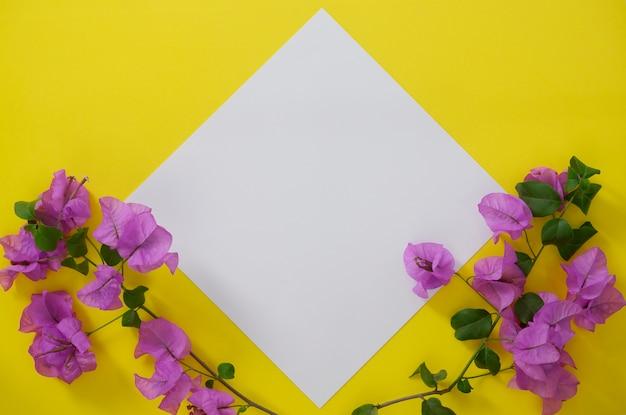 Макет белой бумаги с пространством для текста или изображения на желтом фоне и цветов.
