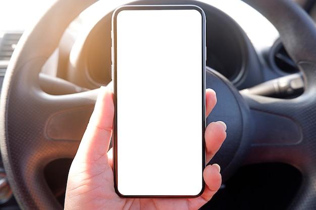 テキストの車の空の明確な画面で携帯電話を持つドライバーの手をモックアップします。