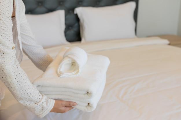 女性は小さなタオルと白いタオルを置いています。ホテルのベッドの上。