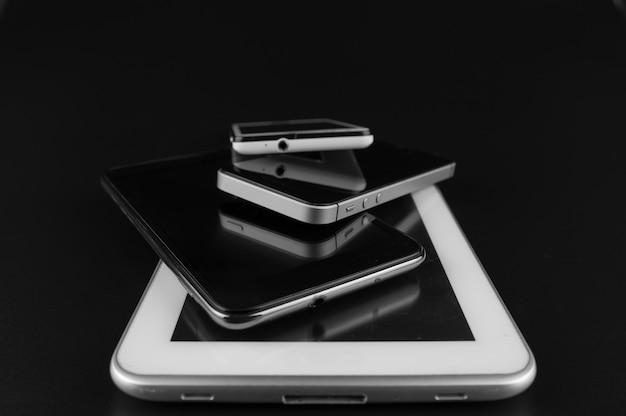 黒い机の上のハイエンドのスマートフォンのスタック。