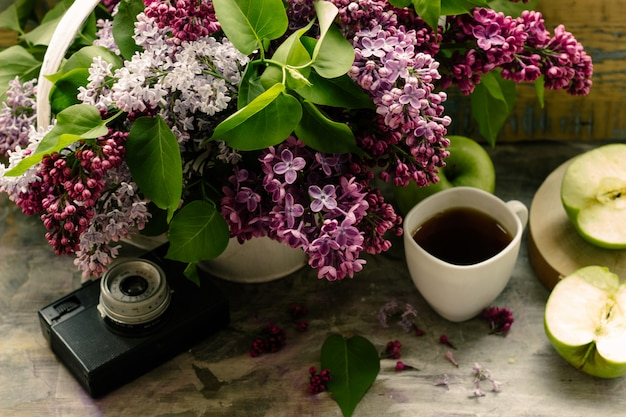 美しい紫ピンクのライラックの花束と熱いお茶のカップ