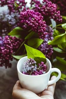 Букет из красивой пурпурно-розовой сирени и чашка горячего чая