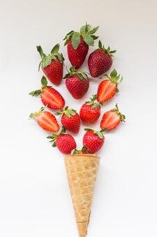 白い背景の上のワッフルコーンのジューシーなストロベリーアイスクリーム