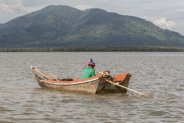 Старый рыбак на старой деревянной лодке.