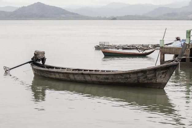Старые деревянные лодки, плавающие в море.