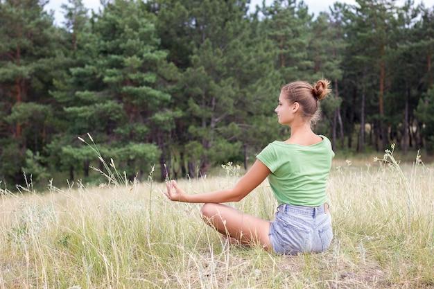 森の瞑想の女の子。自然の中で一人の少女。碑文の下に置く