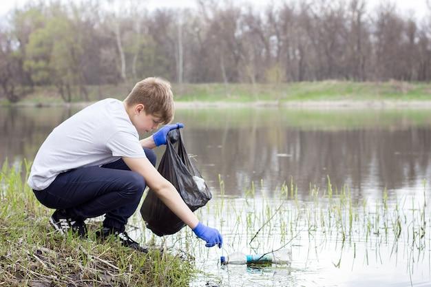 若いボランティアの男は、春の川のほとりでゴミを拾います