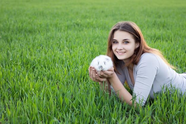 Девушка держа кролика пока на зеленом луге.