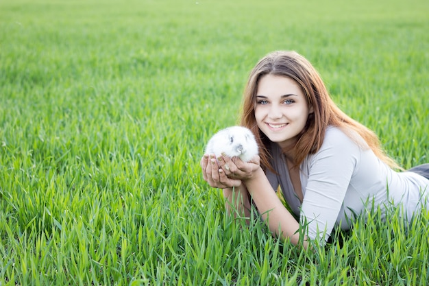 緑の牧草地でウサギを保持している女の子。