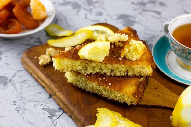 Домашняя выпечка с лимонным чаем. зимняя выпечка, с местом под надписью. домашний лимонный пирог с зимними фруктами