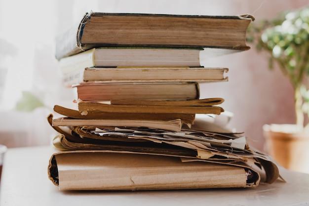 Стопки книг и газет на белом столе в светлой комнате. книги в библиотеке, архив данных, записи. концепция всемирного дня книги