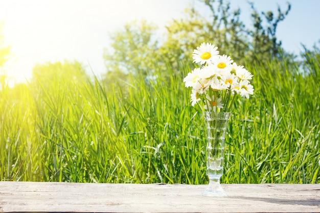 木製のテーブルの上に花瓶にヒナギク。