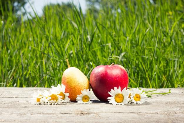 フルーツとヒナギクの花瓶、木製の背景にフルーツのある静物