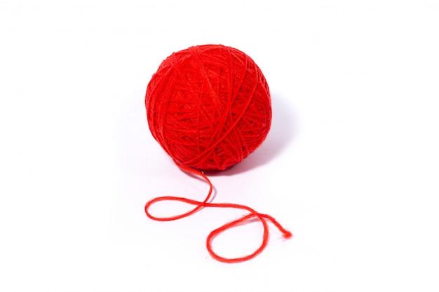 白で隔離され、毛糸の赤いボール