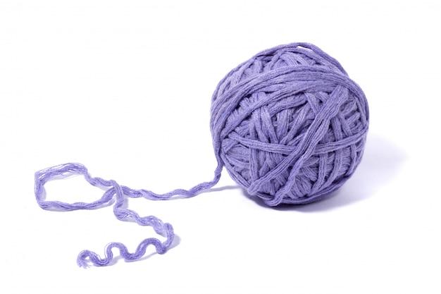 白で隔離されるスレッドの紫色のウールのボール