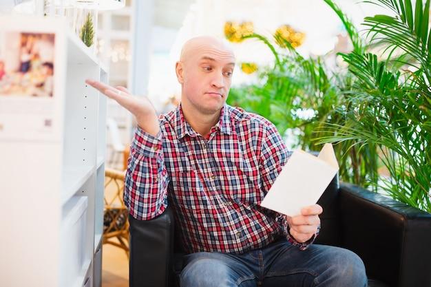 Человек сидит в кресле в светлой квартире с удивлением читает книгу