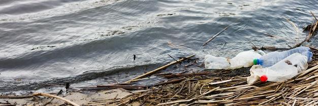 海のゴミのバナー。碑文の場所がある汚染された海岸線。