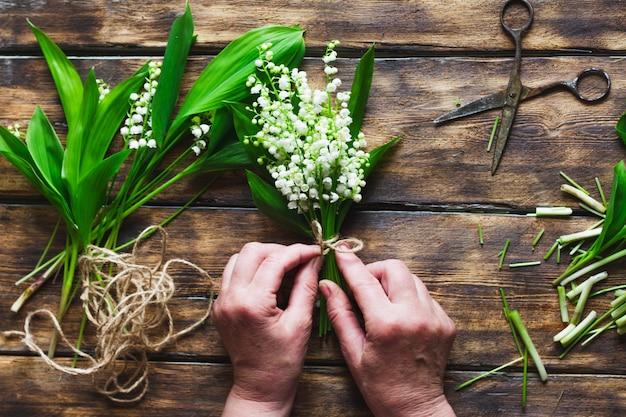 少女は、暗い木の谷にユリの谷の花束を編む