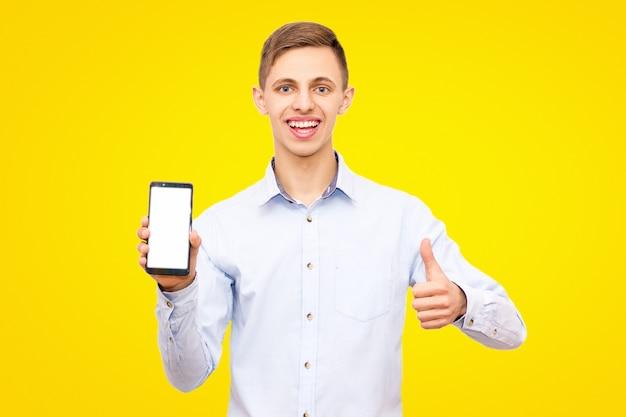 青いシャツを着た男は親指を現して、スタジオで黄色の背景に分離された携帯電話を宣伝します。