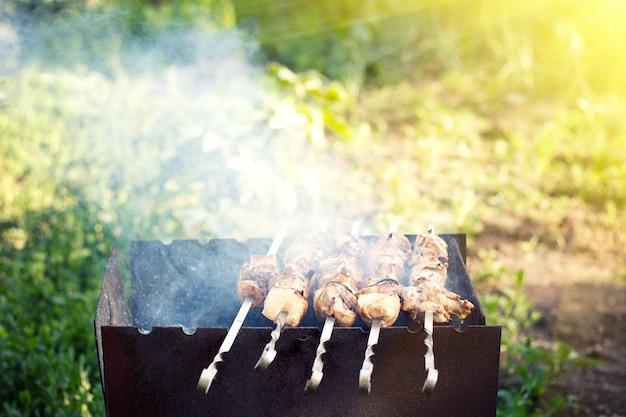自然の中で焼くローストバーベキュー。鶏肉と豚肉の盛り合わせ、およびバーベキューグリルでの夏のファミリーディナー