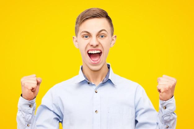 Парень в синей рубашке радуется победе на желтом фоне, поднял руки вверх