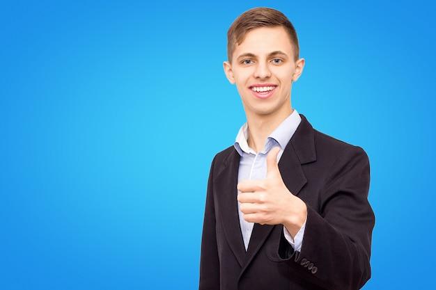 ジャケットと青いシャツを着た男は青い背景上に分離されて彼の指を示しています
