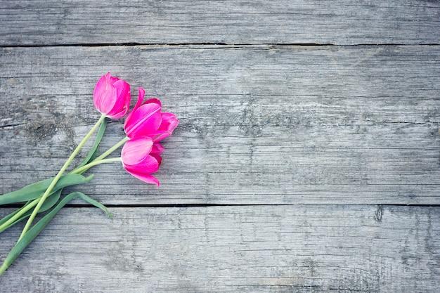 Красные тюльпаны на деревянной предпосылке. красный и белый. вид сверху с пространством для вашего текста.