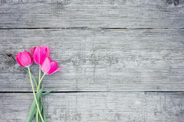 Красные тюльпаны на деревянной предпосылке. красный и белый.