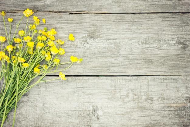 木製の背景に黄色の野の花。黄色の概念