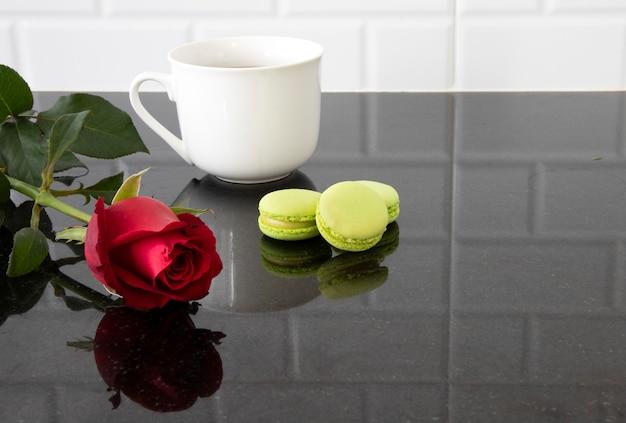マカロンと赤いバラの白いセラミックカップ