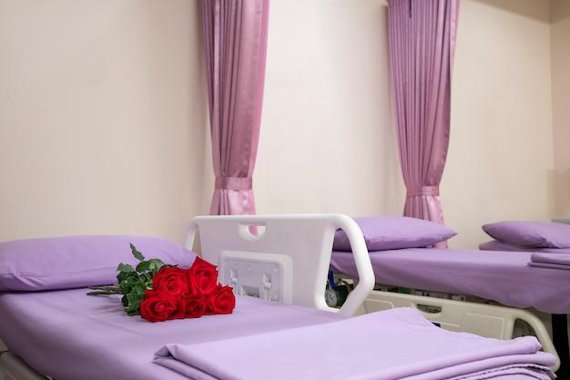 空の病院のベッドの上のバラの花束。