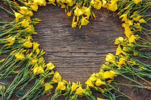 Сердце из желтых цветов на деревянных фоне, любовь и романтика концепции, копией пространства