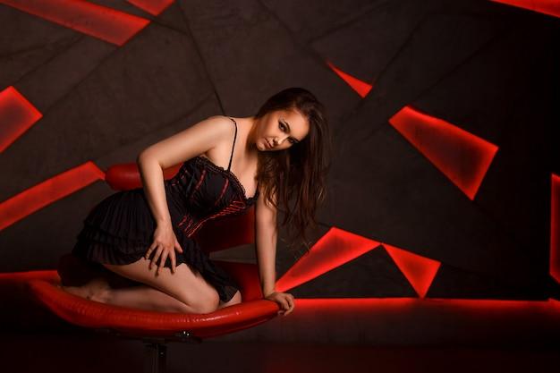 美しいドレスでゴージャスな魅力的な女性は革のソファに座っています。