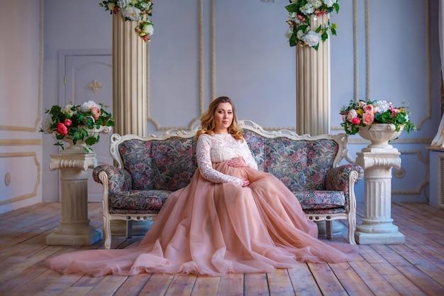 ソファの上の美しいドレスに座っている妊娠中の女性。母性の概念