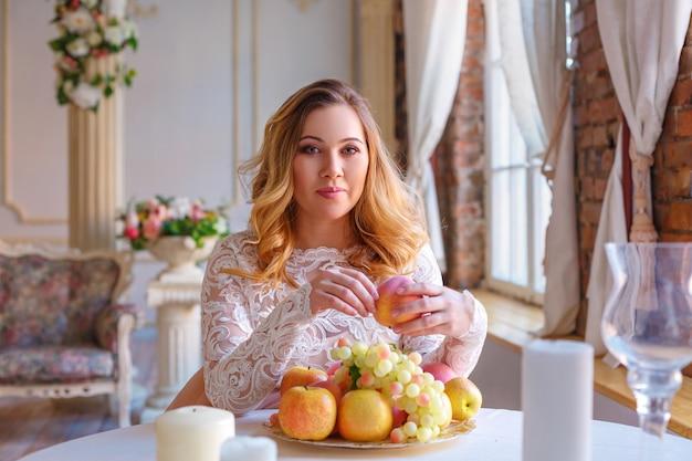若くてきれいな女性は、インテリアの果物でいっぱいのテーブルで桃を食べる