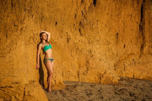 晴れた暑い日に海沿いのビーチでポーズの水着の美しい少女。