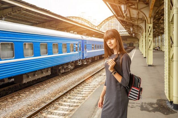 鉄道駅のプラットホームの上に立っている美しい若い女性。