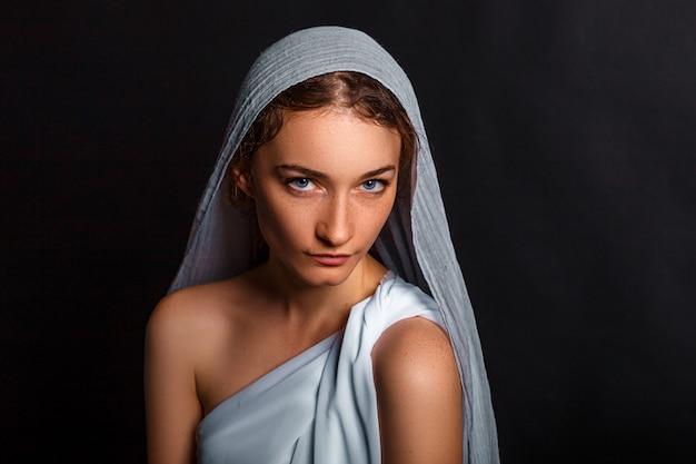 彼女の頭の上のスカーフ、および彼女の手、控え目な表情、信じる女性のロザリオの美しい若い女性。