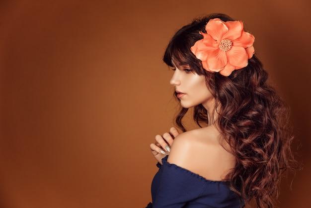 彼女の髪と化粧、花の調子を整えることで花を持つ若い美しい女性