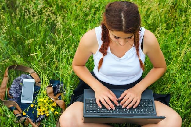 トップビュー、草の上のラップトップで座っている学生